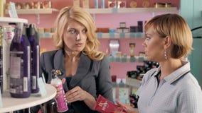 Jeunes filles choisissant le nouveau ton de vernis à ongles à la boutique cosmétique, meilleurs amis dans le supermarché Photos stock