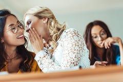 jeunes filles d'étudiant bavardant dans la classe tandis que camarade de classe travaillant dur Photos libres de droits
