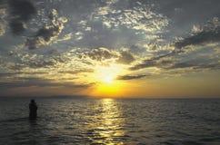 Jeunes filles dans l'eau chaude au coucher du soleil Couleurs magnifiques en ciel et mer Les gens se tenant et observant au couch Photographie stock libre de droits