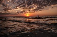 Jeunes filles dans l'eau chaude au coucher du soleil Couleurs magnifiques en ciel et mer Les gens se tenant et observant au couch Images libres de droits