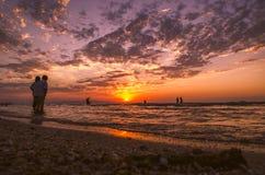 Jeunes filles dans l'eau chaude au coucher du soleil Couleurs magnifiques en ciel et mer Les gens se tenant et observant au couch Photographie stock