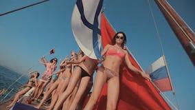 Jeunes filles dans le bikini détendant sur un yacht avec le rouge clips vidéos