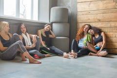 Jeunes filles dans les vêtements de sport ayant le repos après la formation de forme physique photo libre de droits
