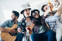 Jeunes filles de danse heureuses jouant la guitare et faire la fête Image libre de droits