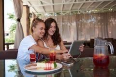 jeunes filles de hippie observant la vidéo sur le pavé tactile tout en se reposant dans le restaurant confortable pendant le temp Photos stock