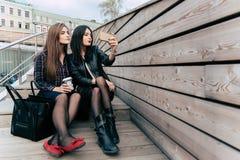 Jeunes filles de hippie se photographiant sur l'appareil-photo mobile tout en détendant après marche, secteur d'espace de copie Photos stock