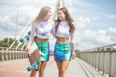 Jeunes filles de sourire avec la pose de planche à roulettes extérieure Images libres de droits