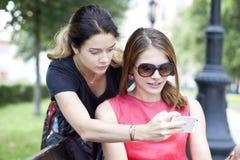 Jeunes filles de sourire avec le téléphone portable se reposant sur un banc en parc Photographie stock