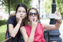 Jeunes filles de sourire avec le téléphone portable se reposant sur un banc en parc Photos libres de droits