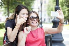 Jeunes filles de sourire avec le téléphone portable se reposant sur un banc en parc Photo stock