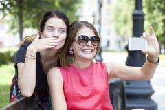 Jeunes filles de sourire avec le téléphone portable se reposant sur un banc en parc Image libre de droits