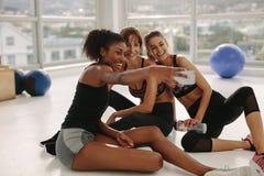 Jeunes filles de sourire prenant le selfie dans le gymnase Photo stock