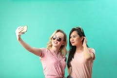 Jeunes filles diverses heureuses prenant le selfie avec le smartphone contre le mur bleu photos libres de droits