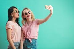 Jeunes filles diverses heureuses prenant le selfie avec le smartphone contre le mur bleu Photographie stock