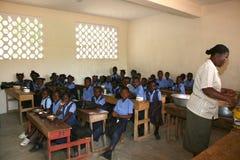 Jeunes filles et garçons haïtiens d'école avec le professeur dans la salle de classe Photographie stock libre de droits
