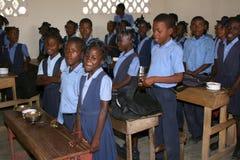 Jeunes filles et garçons haïtiens d'école chantant dans la salle de classe à l'école Images libres de droits