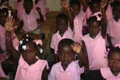 Jeunes filles et garçons haïtiens d'école dans la salle de classe à l'école Images libres de droits