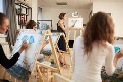 Jeunes filles et images de dessin de peinture de professeur se reposant aux chevalets dans le studio d'art photos stock
