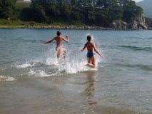 Jeunes filles exécutant à la mer Images stock