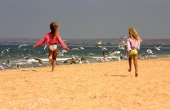 Jeunes filles exécutant heureusement vers des mouettes Photos stock