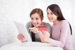Jeunes filles faisant des emplettes sur l'Internet Image stock
