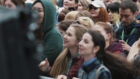 Jeunes filles gaies dans la foule au festival de musique sautant derrière la clôture banque de vidéos