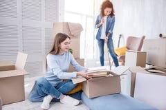 Jeunes filles gaies nettoyant l'appartement et le déballage Images libres de droits