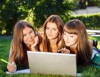 Jeunes filles heureuses d'étudiant à l'aide d'un ordinateur portable à l'extérieur Images stock