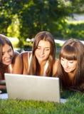 Jeunes filles heureuses d'étudiant à l'aide d'un ordinateur portable Photographie stock