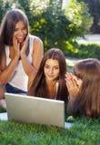Jeunes filles heureuses d'étudiant ayant l'amusement utilisant un ordinateur portable Photo libre de droits