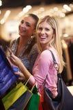 Jeunes filles heureuses dans le centre commercial Image stock