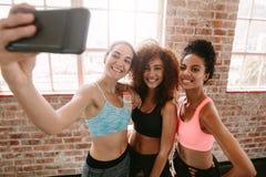 Jeunes filles heureuses dans les vêtements de sport prenant le selfie dans le gymnase Photos stock