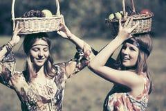Jeunes filles heureuses de mode avec une corbeille de fruits marchant dans le pré d'été Photos stock