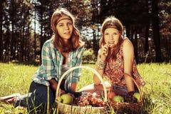Jeunes filles heureuses de mode avec une corbeille de fruits sur la nature Images stock