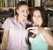Jeunes filles heureuses faisant le visage drôle tout en prenant des photos  Images libres de droits
