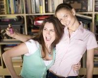 Jeunes filles heureuses faisant le visage drôle tout en prenant des photos Photographie stock