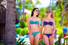 Jeunes filles heureuses marchant sur la plage tropicale, pendant des vacances d'été Image libre de droits