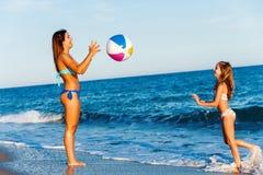 Jeunes filles jouant avec la boule sur la plage Photographie stock