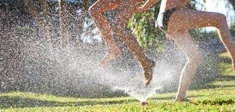 Jeunes filles jouant sauter dans une arroseuse de pelouse de l'eau de jardin image libre de droits