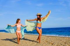 Jeunes filles joyeuses courant avec des foulards de couleur Image stock