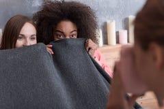 Jeunes filles joyeuses couvertes de couverture dans la chambre à coucher Images stock