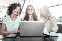 Jeunes filles joyeuses s'asseyant et travaillant avec l'ordinateur portable Images libres de droits