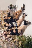 jeunes filles multi-ethniques de sourire se trouvant sur le plancher photographie stock