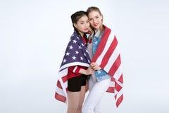 Jeunes filles multi-ethniques se tenant ensemble et regardant l'appareil-photo avec le drapeau des Etats-Unis Photos libres de droits