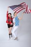 Jeunes filles multi-ethniques tenant et tenant le drapeau de ondulation des Etats-Unis d'isolement sur le gris Photographie stock