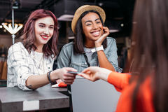 Jeunes filles multiculturelles faisant des emplettes et payant avec la carte de crédit dans la boutique Photo stock