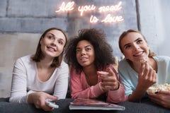 Jeunes filles positives discutant le film se trouvant sur le lit Photographie stock libre de droits