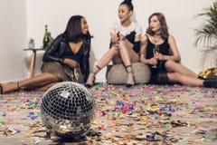 jeunes filles reposant et buvant du champagne à la partie avec la boule de disco photographie stock