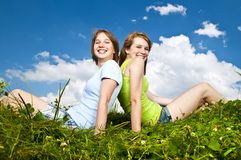 Jeunes filles s'asseyant dans le pré Images stock