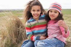 Jeunes filles s'asseyant parmi des dunes sur la plage de l'hiver Image libre de droits